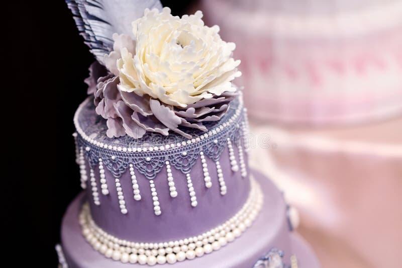 Pastel de bodas púrpura adornado con las flores fotografía de archivo libre de regalías
