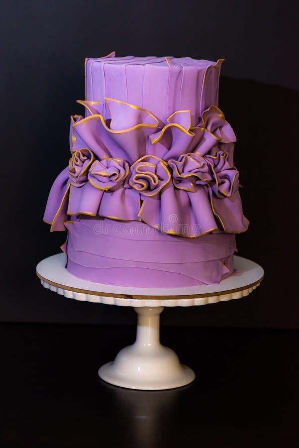 Pastel de bodas púrpura con las flores foto de archivo libre de regalías