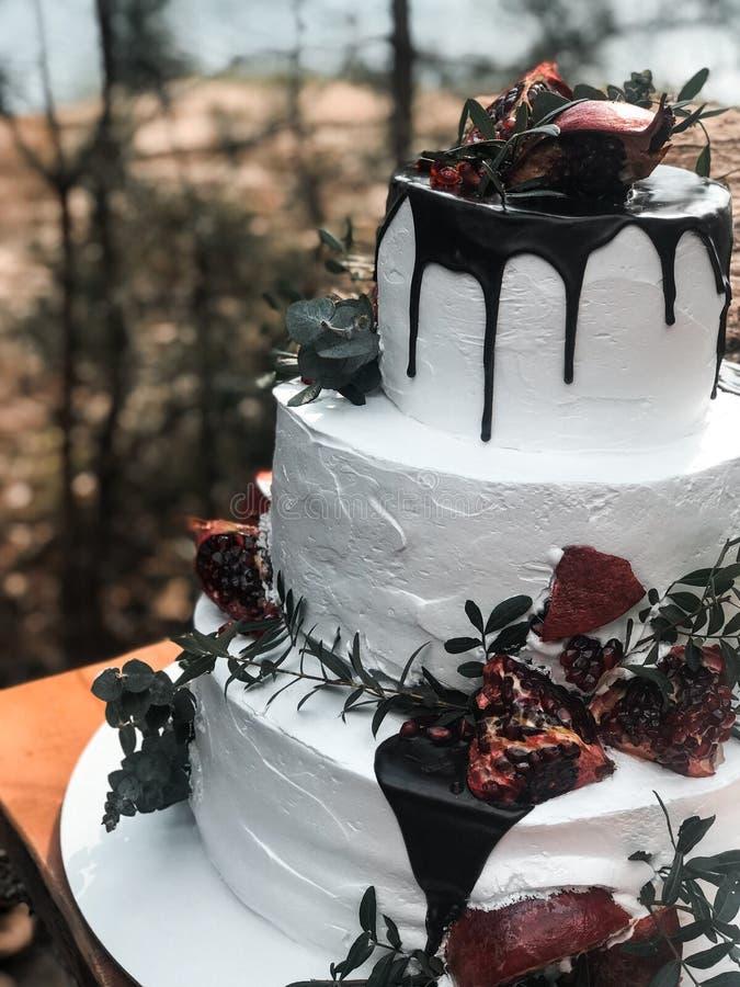 Pastel de bodas poner crema blanco tres-con gradas hermoso con la fruta de la granada y las flores frescas imagen de archivo