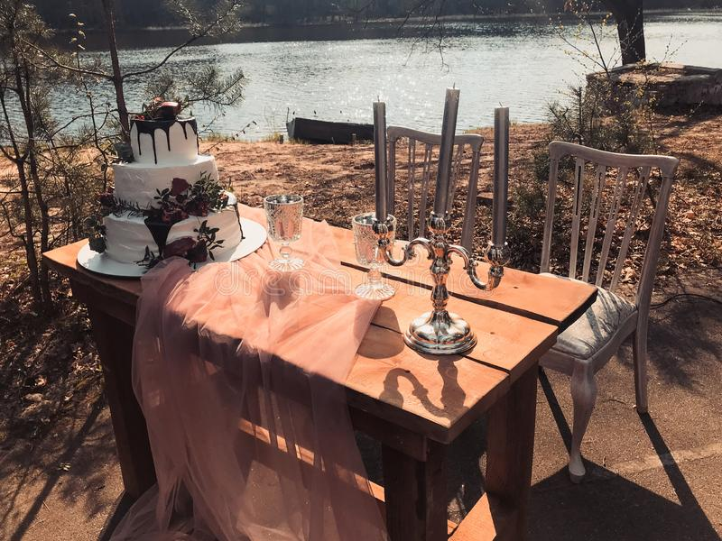Pastel de bodas poner crema blanco tres-con gradas hermoso con la fruta de la granada y las flores frescas en la tabla y las vela imagen de archivo