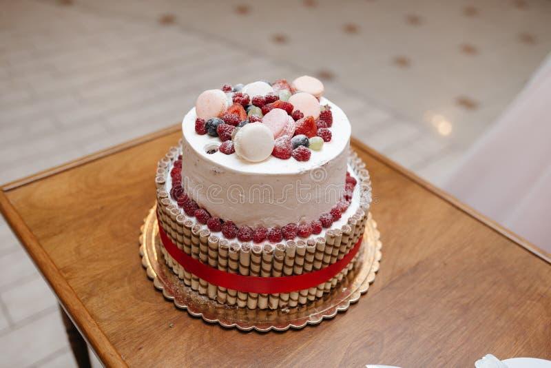 Pastel de bodas rojo y blanco con los macarons y las bayas frescas imagen de archivo