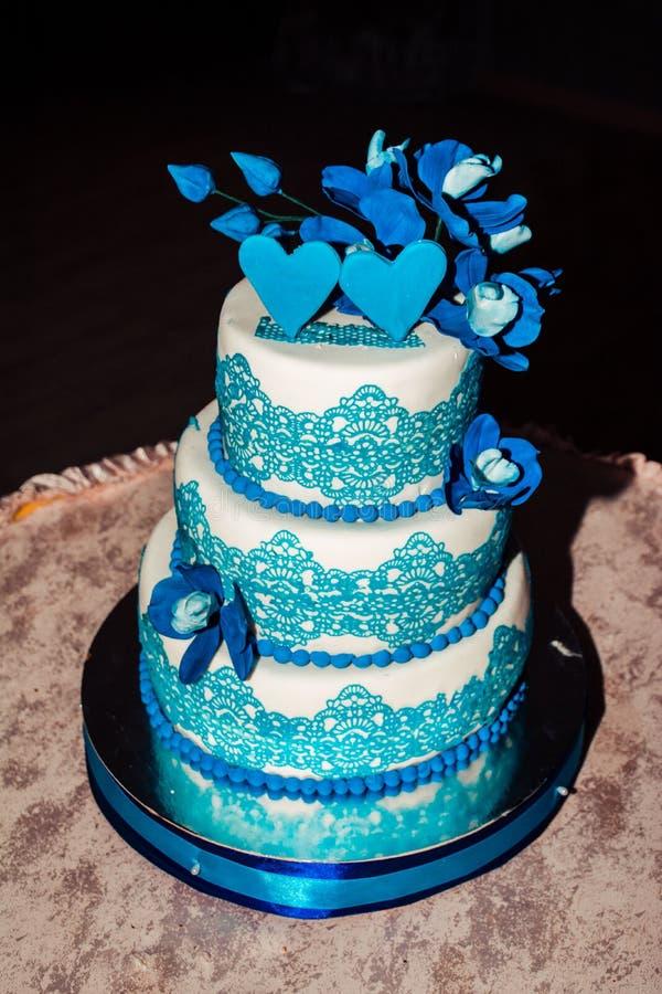 Pastel de bodas de tres gradas con una frontera azul en la celebración de la boda fotografía de archivo libre de regalías