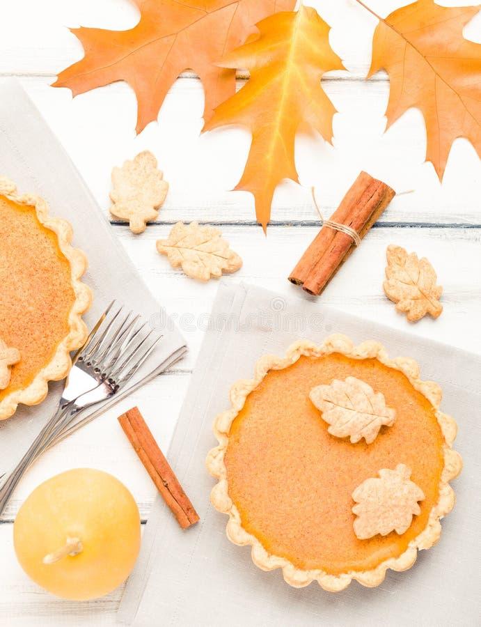 Pastel de calabaza con canela y galletas en servilletas grises en el fondo de madera blanco con las hojas amarillas del otoño fotografía de archivo libre de regalías
