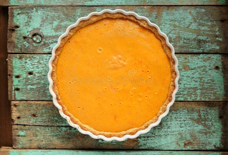 Pastel de calabaza hecho en casa anaranjado brillante redondo fresco en d que cuece blanca imagen de archivo