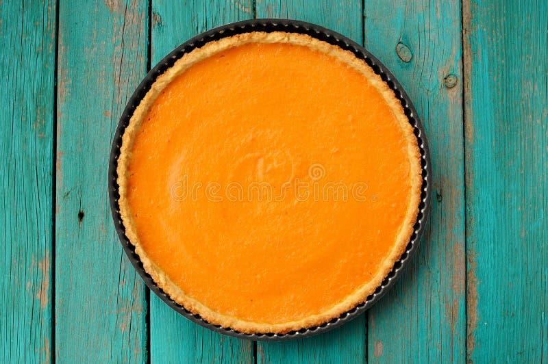 Pastel de calabaza hecho en casa anaranjado brillante redondo fresco en plato de la hornada encendido imagen de archivo