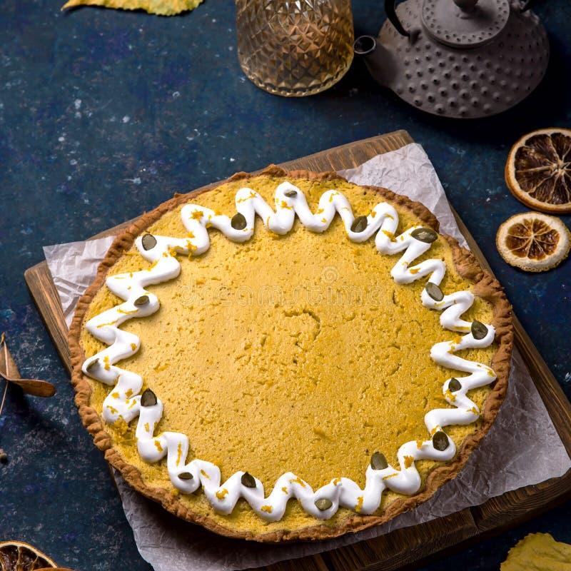 Pastel de calabaza redondo delicioso picante adornado con las semillas blancas de la crema y de calabaza fotografía de archivo