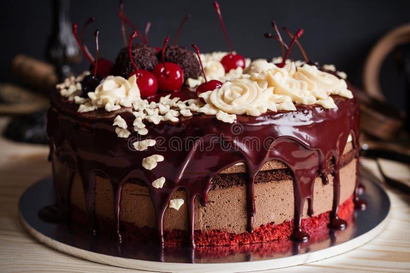 Pastel de capas adornado con el esmalte del chocolate, las flores poner crema y el che fotografía de archivo libre de regalías