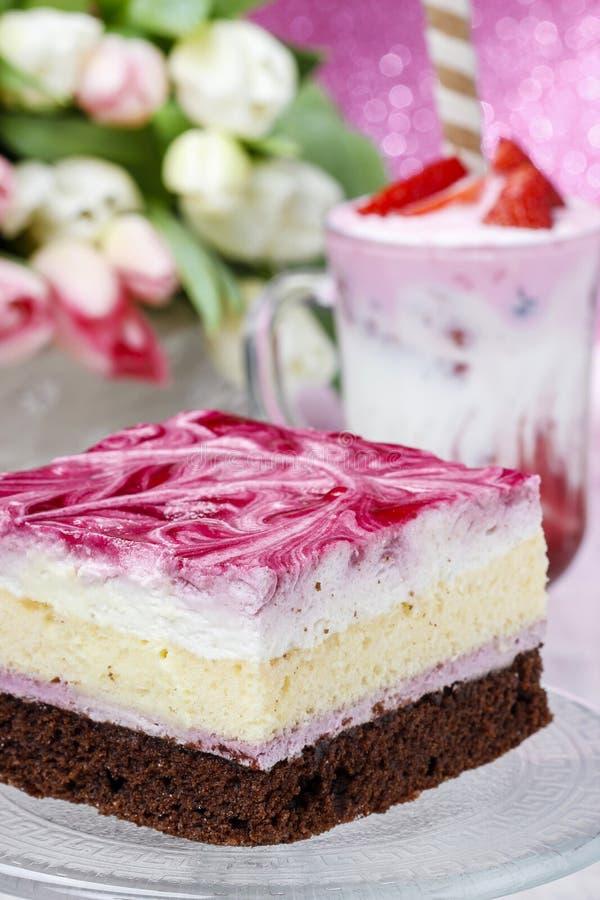 Pastel de capas con la formación de hielo rosada Taza de batido de leche de la fresa fotografía de archivo