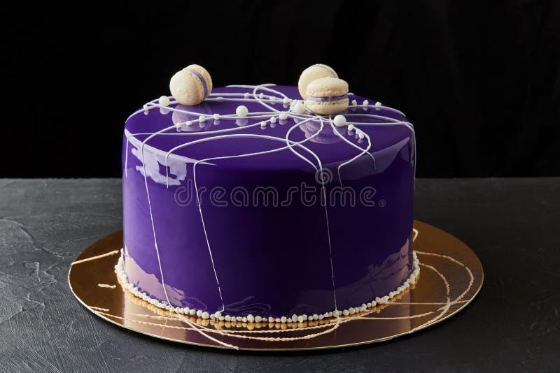 Pastel de capas multi del feliz cumpleaños Con la formación de hielo y macarrones púrpuras Tema del púrpura y blanco imagen de archivo