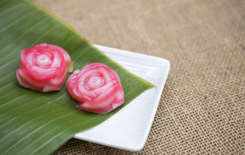 Pastel de capas tailandés de la forma rosada dulce de la flor en la hoja verde fresca del plátano fotografía de archivo