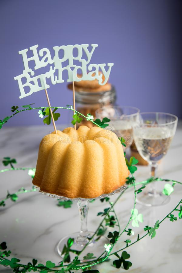 Pastel de cumpleaños, galletas, galletas, muffins y champán con decoración de trébol sobre mesa de mármol y fondo lilaco fotos de archivo