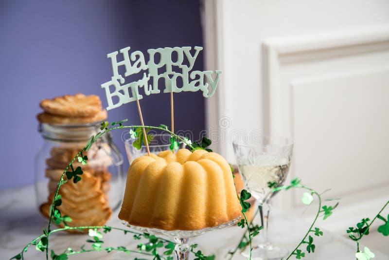 Pastel de cumpleaños, galletas, galletas, muffins y champán con decoración de trébol sobre mesa de mármol y fondo lilaco foto de archivo