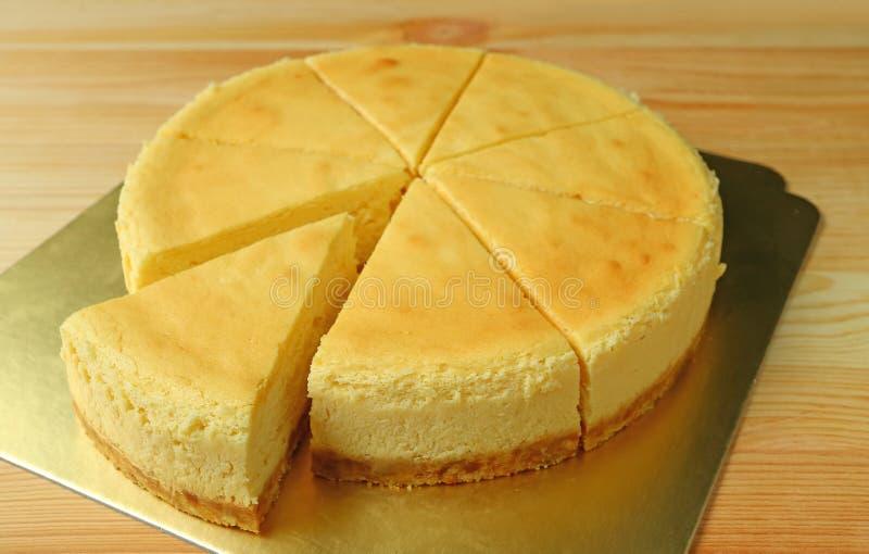Pastel de queso cocido llano amarillo cremoso delicioso con el corte de una pieza de la torta entera fotos de archivo