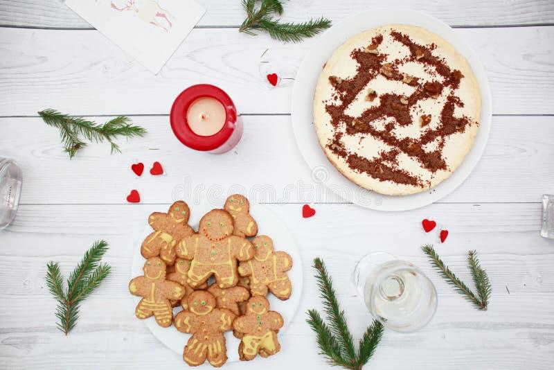 Pastel de queso con el chocolate en la opinión superior del fondo de madera Ramas del abeto Galletas del hombre de pan de jengibr imagen de archivo libre de regalías