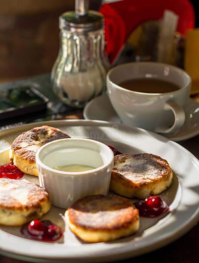 Pastel de queso con la cereza y el café en una placa fotos de archivo