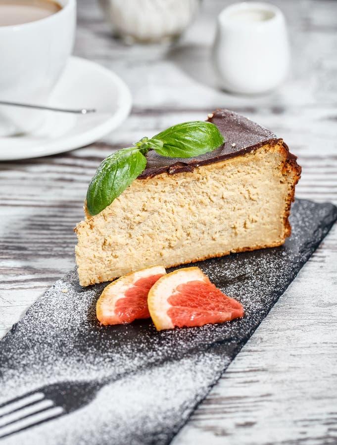 Pastel de queso con la formación de hielo del chocolate junto con dos rebanadas de pomelo fotografía de archivo