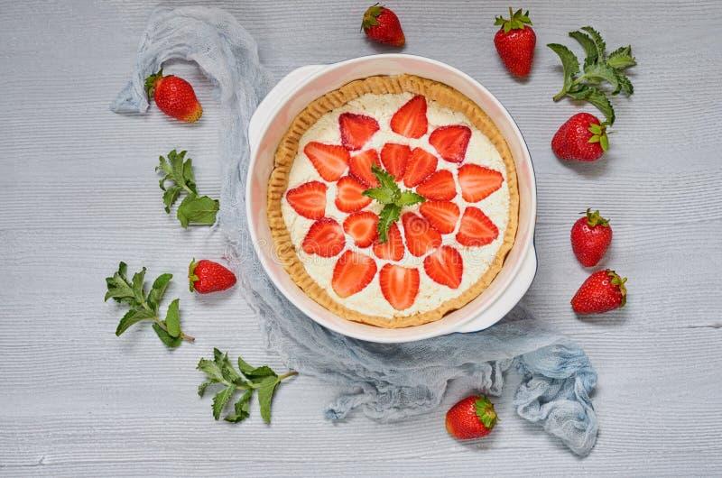 Pastel de queso crudo en un plato de la hornada en el fondo gris adornado con muchas fresas frescas, hojas de la fresa de menta imágenes de archivo libres de regalías