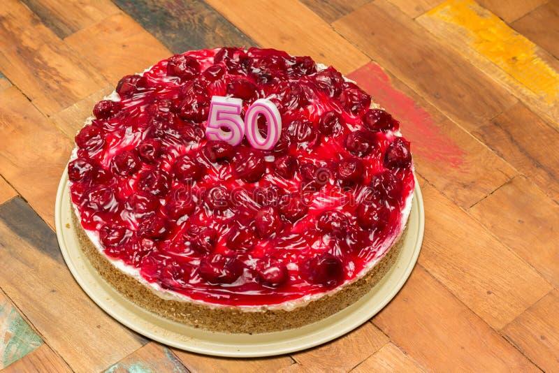 Pastel de queso de la cereza con las velas para el 50.o cumpleaños imagen de archivo