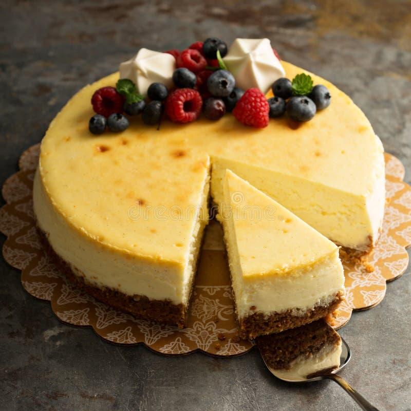 Pastel de queso de Nueva York en un soporte de la torta fotos de archivo