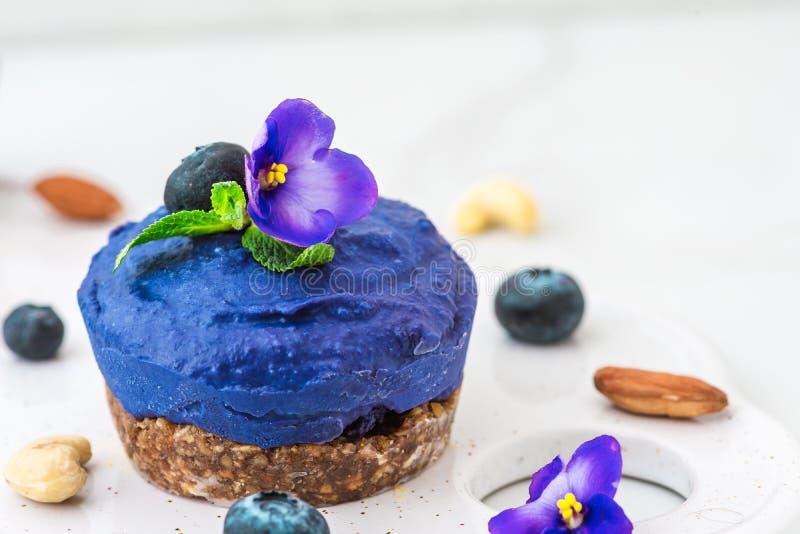 Pastel de queso del anacardo del vegano de la flor del guisante del arándano y de mariposa con las bayas frescas, flores comestib foto de archivo