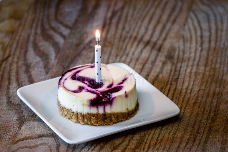 Pastel de queso del arándano con una vela imagen de archivo
