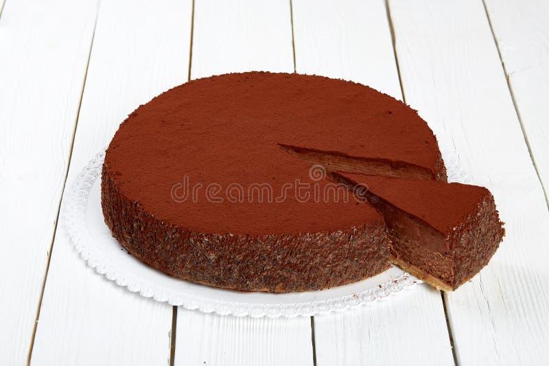 Pastel de queso del chocolate en una tabla de madera blanca imagenes de archivo