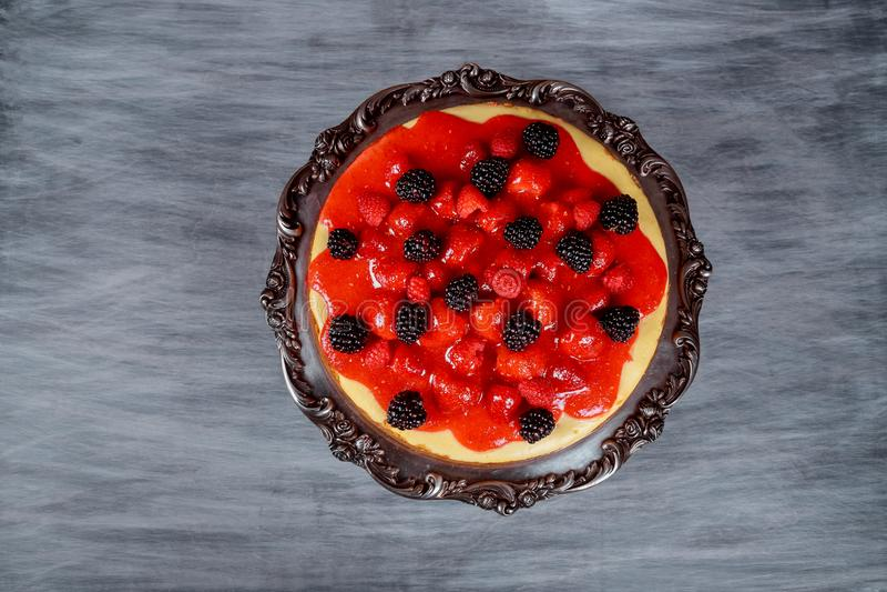 Pastel de queso delicioso con las fresas frescas con el arándano fresco y la crema azotada en la tabla rústica de madera foto de archivo