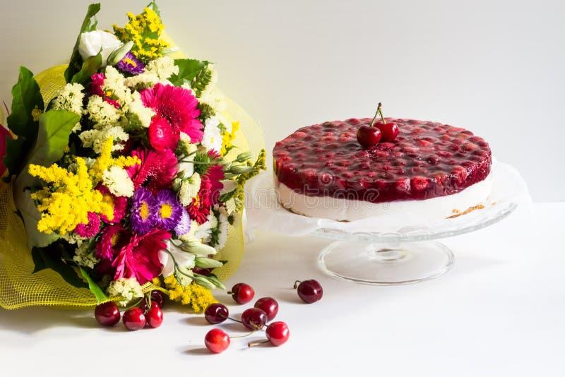 Pastel de queso frío con la jalea y las flores de la cereza foto de archivo libre de regalías