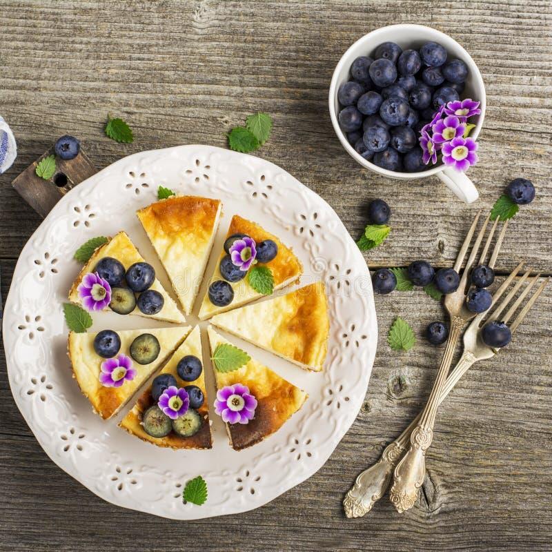 Pastel de queso fresco hecho en casa con los arándanos y las flores comestibles en una placa de cerámica blanca, en un fondo de m foto de archivo