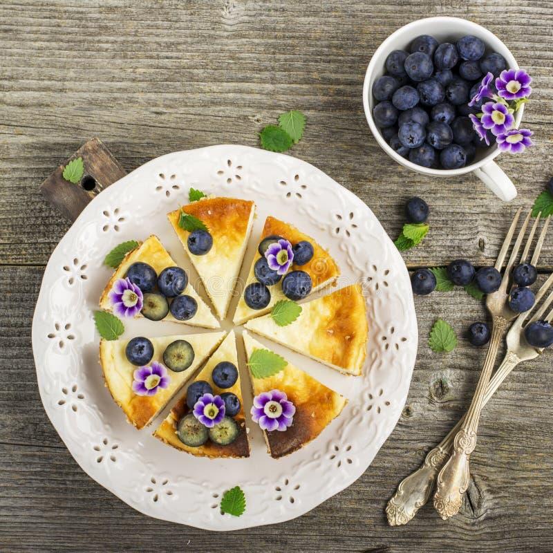 Pastel de queso fresco hecho en casa con los arándanos y las flores comestibles en una placa de cerámica blanca, en un fondo de m fotos de archivo libres de regalías