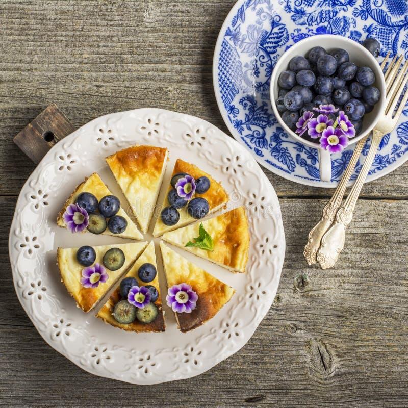 Pastel de queso fresco hecho en casa con los arándanos y las flores comestibles en una placa de cerámica blanca, en un fondo de m imagenes de archivo