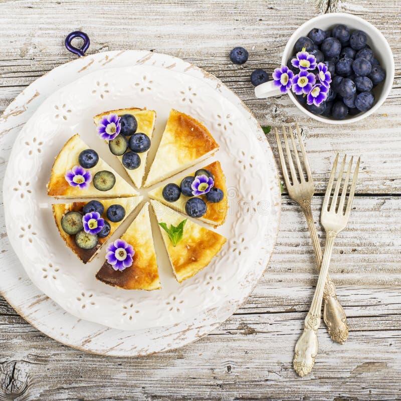 Pastel de queso fresco hecho en casa con los arándanos y las flores comestibles en una placa de cerámica blanca, en un fondo de m fotografía de archivo libre de regalías
