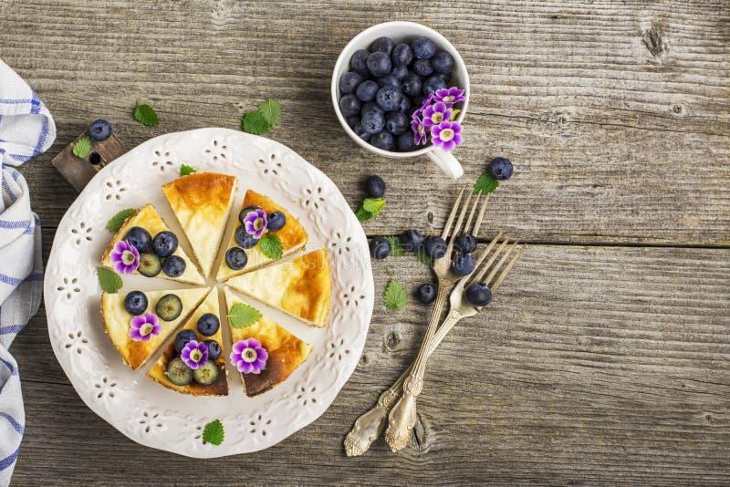 Pastel de queso fresco hecho en casa con los arándanos y las flores comestibles en una placa de cerámica blanca, en un fondo de m imagen de archivo