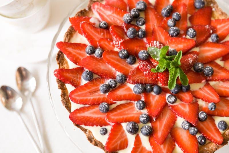 Pastel de queso hecho en casa adornado con las fresas orgánicas, los arándanos, la menta fresca y la crema Empanada agradable por fotos de archivo libres de regalías