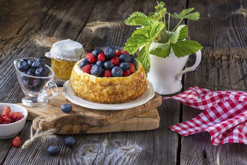 Pastel de queso hermoso con los arándanos y las fresas foto de archivo