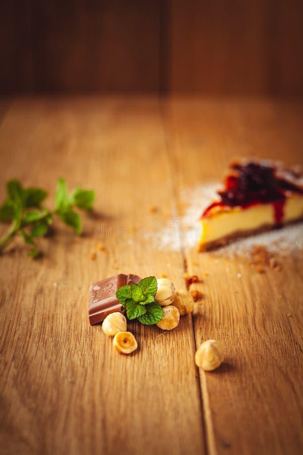 Pastel de queso italiano tradicional hermoso con las frutas, la menta, y el az?car en polvo rojos en el fondo de madera, foco sel foto de archivo