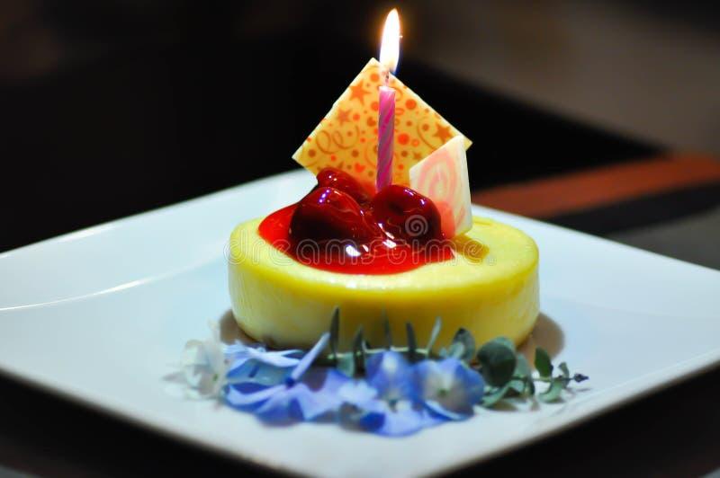 Pastel de queso de la cereza con la vela foto de archivo
