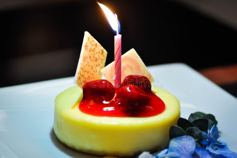 Pastel de queso de la cereza con la vela fotos de archivo