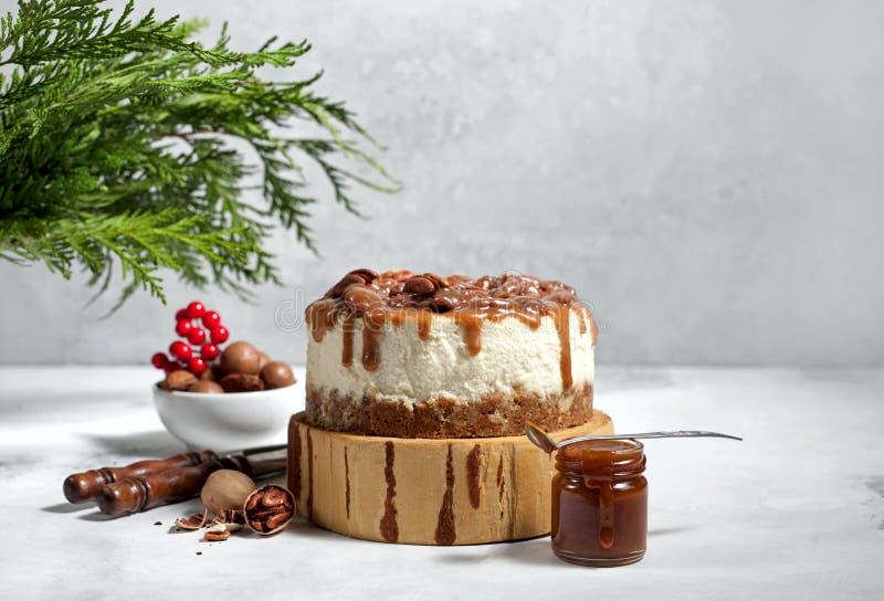 Pastel de queso de la Navidad con las pacanas y la salsa del caramelo imágenes de archivo libres de regalías