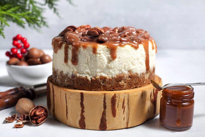 Pastel de queso de la Navidad con las pacanas y la salsa del caramelo fotografía de archivo