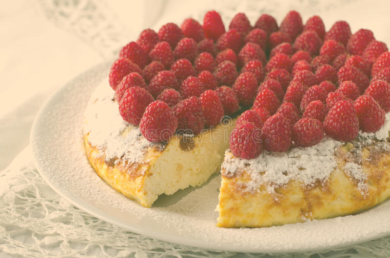 Pastel de queso, soplo, crema batida poner crema, postre del pudín con las frambuesas frescas y hojas de menta en una placa blanc fotografía de archivo libre de regalías