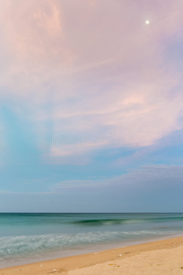 Pastel dusk time on desert beach with moon stock image