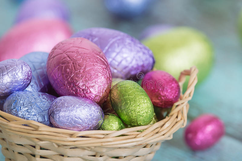 Pastel Easter chocolate eggs in a basket royalty free stock photo