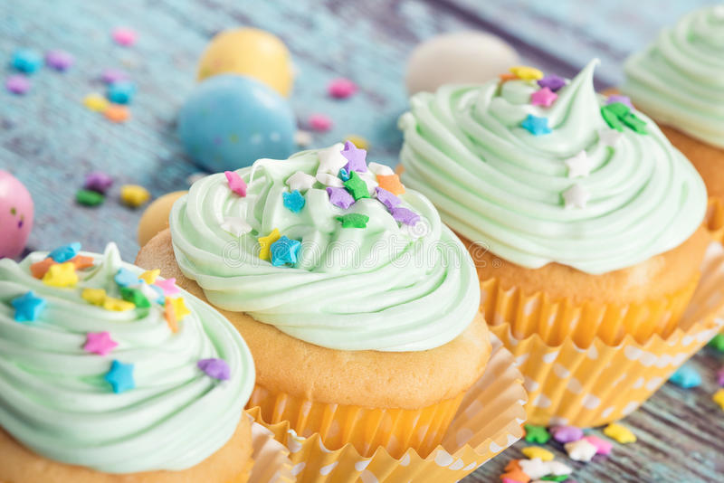 Pastel Easter cupcakes with candy and sprinkles stock photo