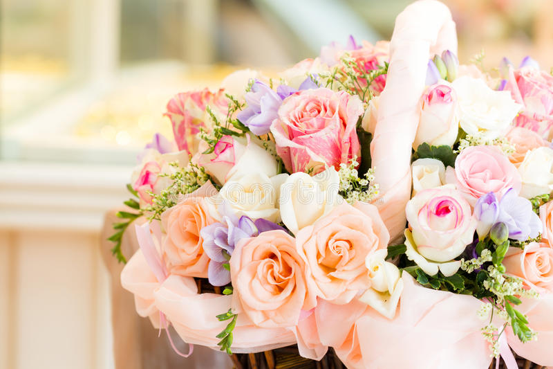 Pastel flowers in basket. Soft pastel roses in weave basket royalty free stock image