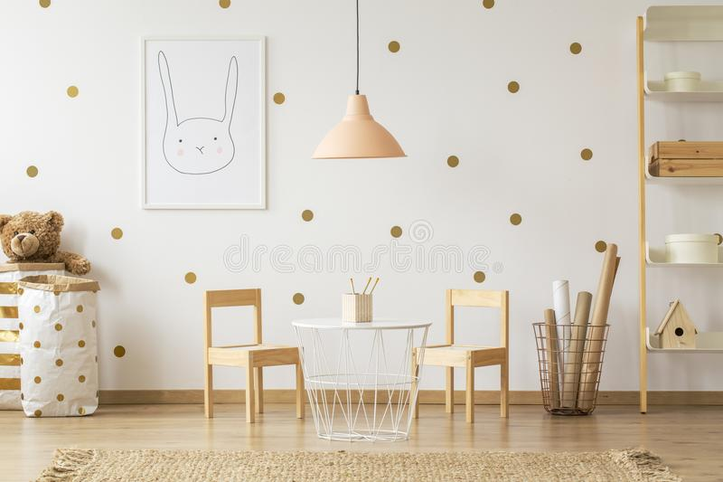 Pastel lamp above table between chairs in gold kid`s room interi royalty free stock images