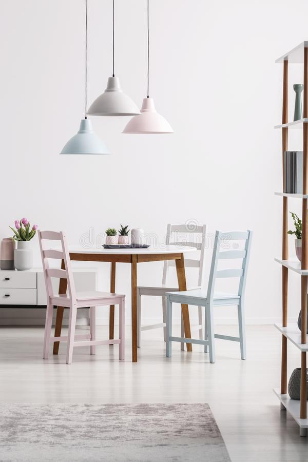 Pastel lamps above table with chairs in white dining room interior with grey carpet. Real photo royalty free stock photos