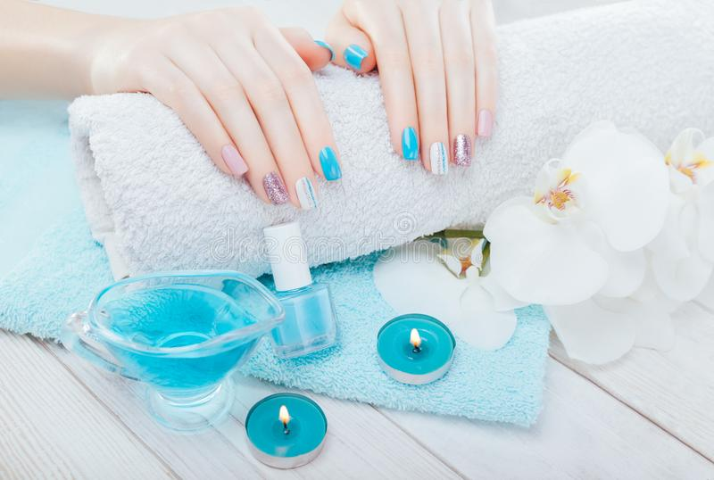 Pastel manicure with orchid and spa essentials. Combination of blue, white, pink colors and sparkles. royalty free stock image