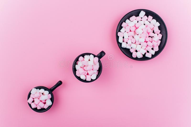 Pastel marshmallow in a cup on a pink background royalty free stock image