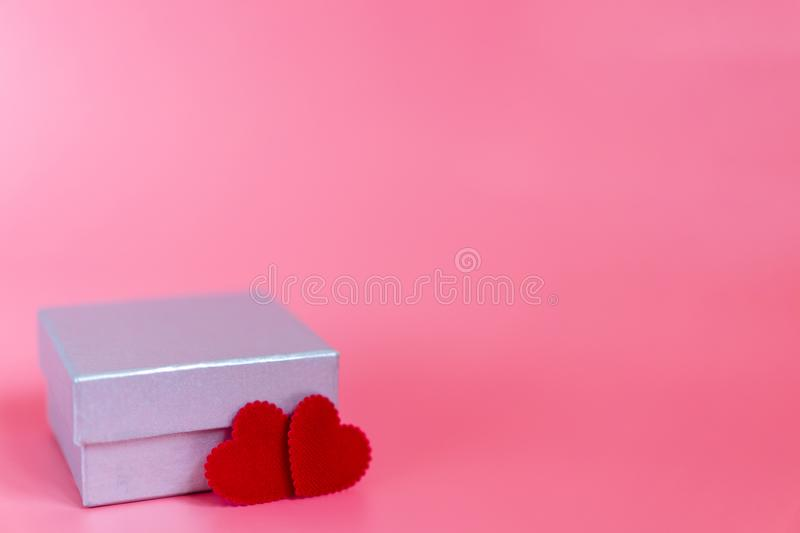 Pastel pink background with a silver gift box and two craft little red heart shape decorate for someone special who beloved. With love and care. Valentines day royalty free stock images